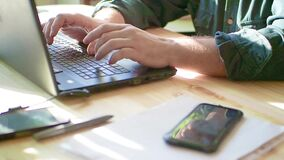 Close-up of male hands using laptop at cafe, man`s hands typing on laptop keyboard in interior, side view of freelancer. Using computer at home stock video