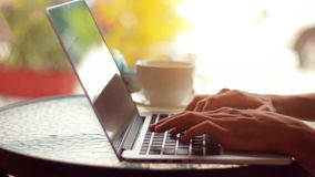 Close-up of male hands using laptop at cafe. Man`s hands typing on laptop keyboard in interior, side view of freelancer using computer in cafe stock video footage