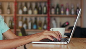 Close-up of male hands using laptop at cafe stock footage