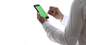 Close-up of male hands using smartphone near the window. Man using mobile phone while standing near window. Chroma key stock video footage
