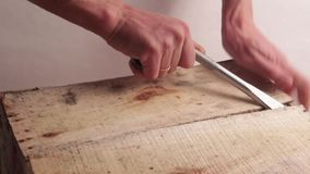 Close-up. Male hands with a wide screwdriver or other mounting tool open a wooden box. Breaking the first plank. Light background. Male hands with a wide stock video
