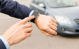 Close up of male hands with wristwatch and car. Transport, business trip, technology, time and people concept - close up of male hands with wristwatch on car Stock Photos