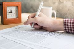Close up of Male hands writing some data in documents on the wooden desk. Business Concept Royalty Free Stock Photos