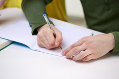 Close up of male hands writing to notebook. People and education concept - close up of male hands writing to notebook at school Stock Photography