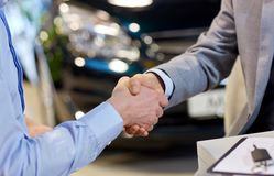 Close up of male handshake in auto show or salon Stock Images