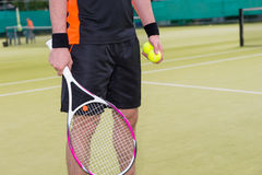 Close-up of male holding tennis balls and racket Stock Photography