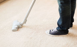 Close up of male hoovering carpet. Cleaning and home concept - close up of male hoovering carpet royalty free stock photo