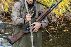 Close up male hunter carry rifle walking in nature lanscape f stock photo