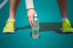 Close up of male jogger holding plastic bottle of water on running track royalty free stock images