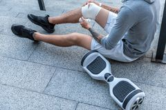 Man bandaging leg on floor outdoor. Close up male knee. He swathing it while locating at street near gyroscooter. Trauma concept stock image