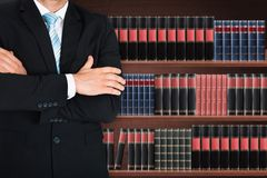 Close-up of male lawyer with arm crossed. Standing In Front Of Book Shelf Royalty Free Stock Photo