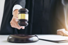 Close up of Male lawyer or judge hand's striking the gavel on so Stock Photography
