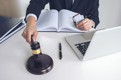 Close up of Male lawyer or judge hand`s striking the gavel on so Stock Image
