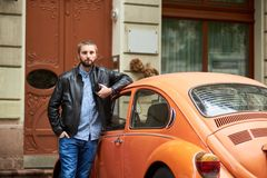 Close-up male leaning on orange retro car with photo camera. Close-up of male with the beard leaning on orange retro car and holding in hand a professional photo Royalty Free Stock Image