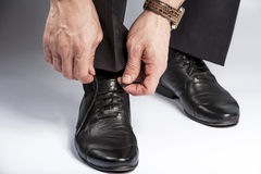 Close up of male leg and hands tying shoe laces Stock Image