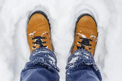 Close-up of male legs in blue jeans and winter shoes on snow.  Royalty Free Stock Images