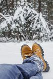 Close-up of male legs in blue jeans and winter shoes on snow Royalty Free Stock Photos