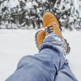 Close-up of male legs in blue jeans and winter shoes on snow.  Royalty Free Stock Image