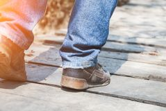 Close-up of male legs in sneakers on bridge. Close-up of male legs in dirt sneakers on a wooden bridge Stock Photos