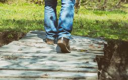 Close-up of male legs in sneakers on bridge. Close-up of male legs in dirt sneakers on a wooden bridge Stock Photography