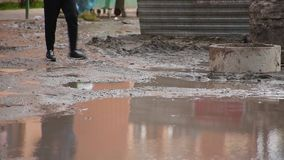 Close-up male legs going at residential yard through broken dirty road with huge puddle in which man is reflected