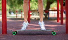 Close-up of male legs on a natural background. A sportive guy jumping on his longboard. Sport, outdoors concept. Copy. Close-up picture of teenagers` legs in Royalty Free Stock Photo