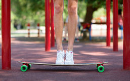 Close-up of male legs on a natural background. A sportive guy standing on his longboard. Sport, outdoors concept. Copy space. Close-up picture of teenagers` Stock Image