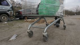 Close-up male pushing cart at garbage dump. Close-up male legs pushing shopping cart with plastic bags at garbage dump with abandoned cars. Homeless man stock video