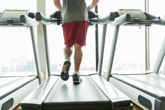 Close up of male legs running on treadmill in gym. Sport, fitness, technology and people concept - close up of male legs running on treadmill in gym Stock Images