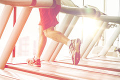 Close up of male legs running on treadmill in gym Stock Photo