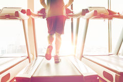 Close up of male legs running on treadmill in gym Stock Images