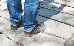 Close-up of male legs in sneakers on bridge. Close-up of male legs in dirt sneakers on a wooden bridge Royalty Free Stock Images