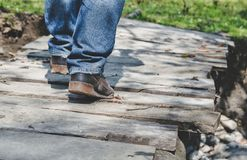 Close-up of male legs in sneakers on bridge. Close-up of male legs in dirt sneakers on a wooden bridge Stock Image