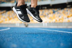 Close up of a male legs in sneakers jumping. At the racetrack Royalty Free Stock Photo