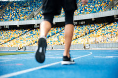 Close up of a male legs in sneakers on a recetrack. At the stadium Royalty Free Stock Photography