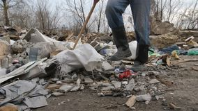 Close-up male legs walking at garbage dump site. Close-up front view of male legs in boots walking at garbage dump site scavenging for plastic and paper to stock video footage