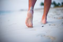 Close up of male legs on white sandy beach. Close up of female feet on white sand beach Royalty Free Stock Image