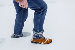Close-up of male legs in winter shoes and blue jeans walking on snow. Royalty Free Stock Photos