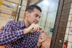 Close-up male lockpicker hand fixing door handle at home Royalty Free Stock Photos