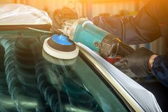 MAn polishes the front glass. Close-up of a male mechanic with a blue prism and protective gloves polishes the front glass of the car with a modern green Royalty Free Stock Image