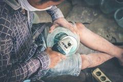 Close-up of a male mechanic with glass polish machine. Bali island Stock Image