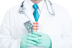 Close-up of male medic holding handful of blisters Stock Photo