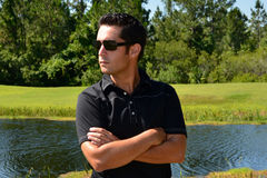 Close Up Of Male Model In Sunglasses. Close Up of male model wearing black golf shirt and sunglasses with arms crossed Royalty Free Stock Photos