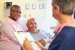 Close Up Of Male Nurse Updating Patient Notes. In Hospital Ward Smiling At Each Other Stock Photo