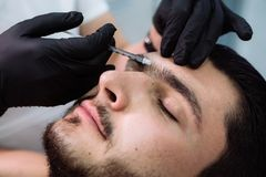 Close up male patient face and cosmetologist`s hands with syringe during facial beauty injections. Cosmetology concept.  Royalty Free Stock Photography