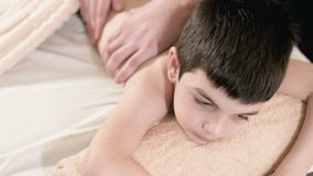 Close-up male physiotherapist masseur makes a healing relaxing massage to a little boy lying on a massage bed. Back stock video