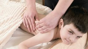 Close-up male physiotherapist masseur makes a healing relaxing massage to a little boy lying on a massage bed. Back stock footage