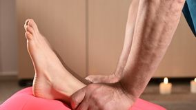 Close-up A male physiotherapist is stretching the knee joints to a young girl patient. Manual Wellness Therapy.  stock video footage