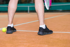 Close up male player`s legs during the game on clay court outdoo. Close up male player`s legs during the game wearing a sportswear on clay court outdoors Royalty Free Stock Photo