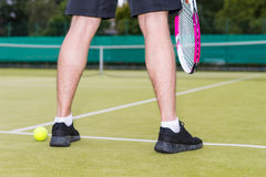 Close up male player`s legs during the game on green grass court Stock Images